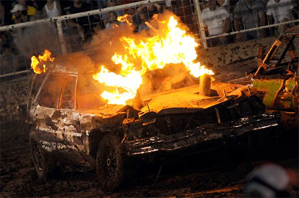 Fire erupts from a car at a demolish derby.